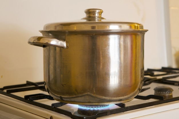 Photo of a pot on the flames of kitchen oven burning gas