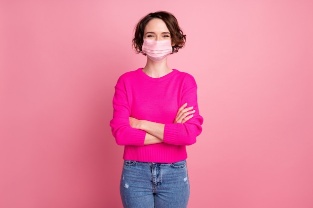 Photo of pretty attractive cheerful lady self-confident person arms crossed good mood wear casual sweater pullover medical mask jeans isolated pink pastel color background