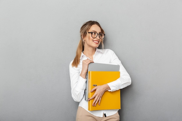 Photo of pretty businesslike woman wearing glasses holding paper folders in the office, isolated