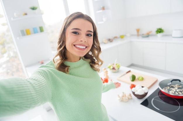 Photo of pretty cheerful girl cooking tasty meal welcoming you make selfie