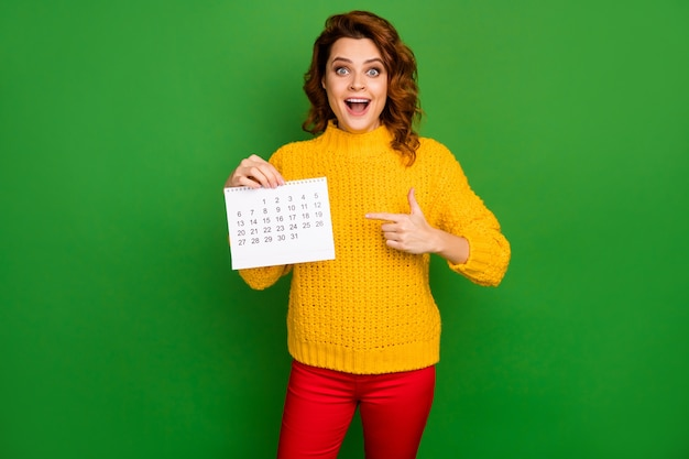 Photo of pretty cheerful lady direct finger paper calendar showing month without plans amazing planner wear yellow knitted sweater red pants isolated green color wall