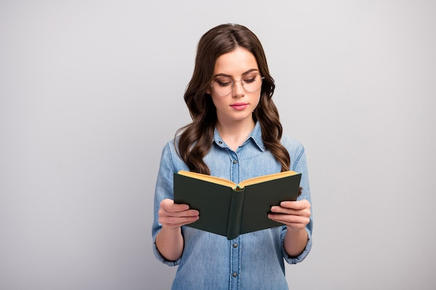 Photo of pretty concentrated business lady hold book hands addicted reader book worm not smiling wear specs casual jeans denim shirt isolated grey color