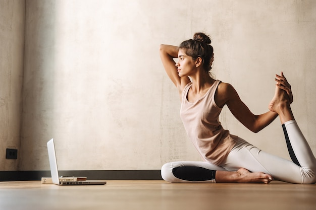 Photo of pretty concentrated woman in sportswear doing yoga exercises using laptop while sitting on floor at home