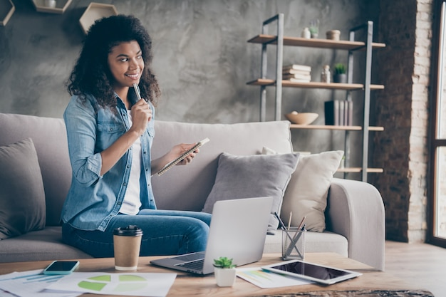 Photo of pretty dark skin curly business lady browsing notebook table holding planner writing week to-do list sitting cozy couch wear casual denim outfit flat indoors