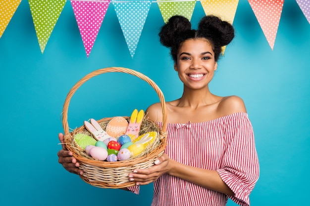 Photo of pretty dark skin lady hold holiday basket came family easter dinner eggs ginger bread bunny hang flags wear red white striped shirt naked shoulders isolated blue color wall