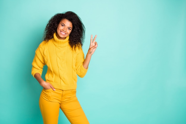 Photo of pretty dark skin wavy lady holding hand showing v-sign symbol positive mood wear yellow knitted pullover and pants isolated blue teal color wall