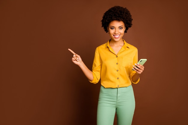 Photo of pretty dark skin wavy lady holding telephone influencer indicating finger empty space show sale app prices wear yellow shirt green trousers isolated brown color