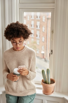 La foto di una donna dalla pelle piuttosto scura ha una pausa caffè con gadget moderni, gode di comunicazione online