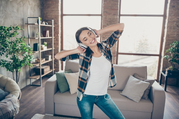 Photo of pretty dreamer lady rejoicing listening favorite melody in modern earflaps dancing in light room near sofa wearing casual clothes apartment indoors