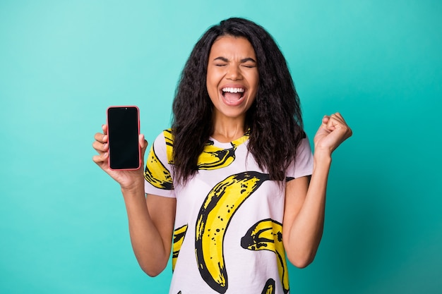Photo of pretty excited lady hold telephone screen empty space closed eyes wear banana print t-shirt isolated teal color background
