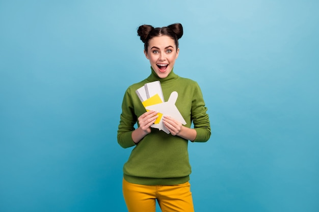 Photo of pretty funny lady hold paper air plane passport tickets addicted traveler buy cheap tour abroad wear green turtleneck yellow trousers isolated blue color wall