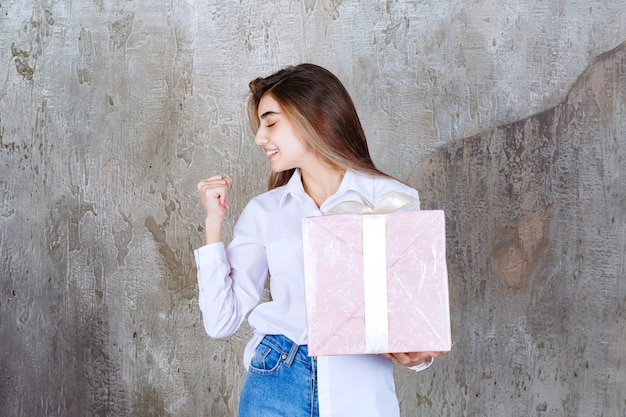 Photo of a pretty girl model with long hair holding big present