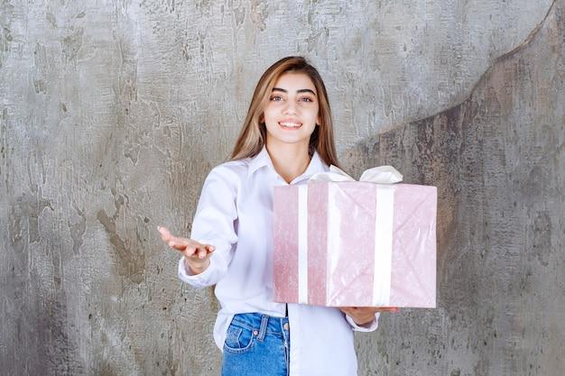Foto di una bella modella con i capelli lunghi che tiene in mano un grande regalo