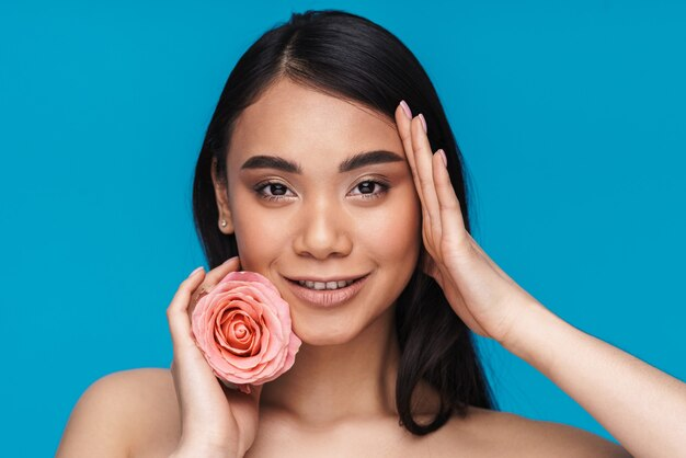 Photo of a pretty happy cheerful asian young woman posing isolated on blue wall with flower.