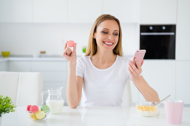 Photo of pretty housewife holding telephone chatting with friends eating colorful macaroons granola breakfast milk on table white light kitchen indoors