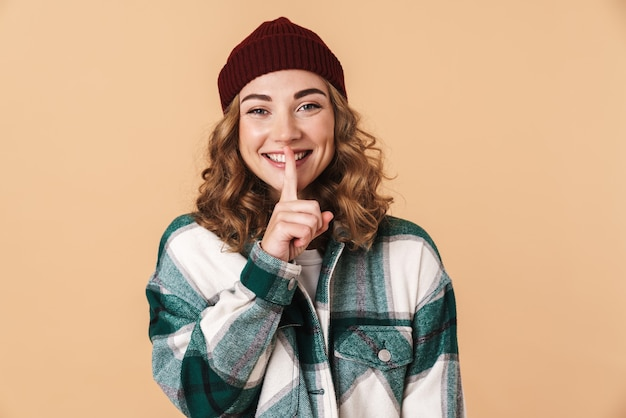 Photo of pretty joyful woman in knit hat making silence gesture and smiling isolated on beige