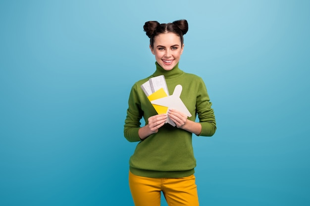 Photo of pretty lady hold paper air plane passport tickets advising flying way of traveling addicted traveler wear green turtleneck yellow trousers isolated blue color wall