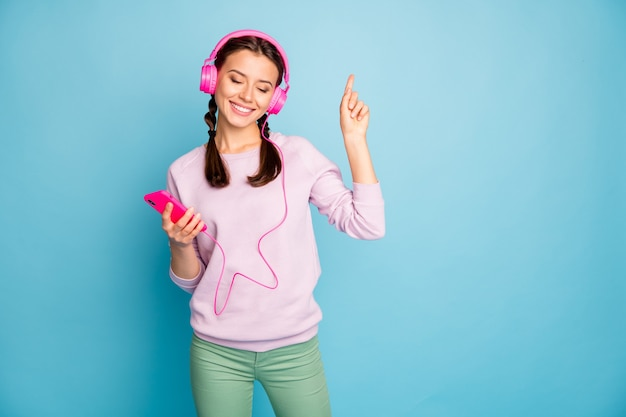 Photo of pretty lady hold telephone bright earphones on ears listen radio eyes closed raising finger rejoicing wear casual stylish pink pullover green trousers isolated blue color