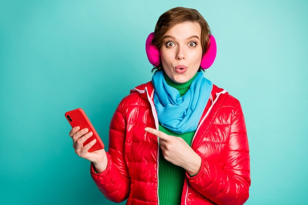 Photo of pretty lady hold telephone hand indicating finger smart phone advising buy low sale price wear red coat scarf pink ear covers green jumper isolated teal color wall