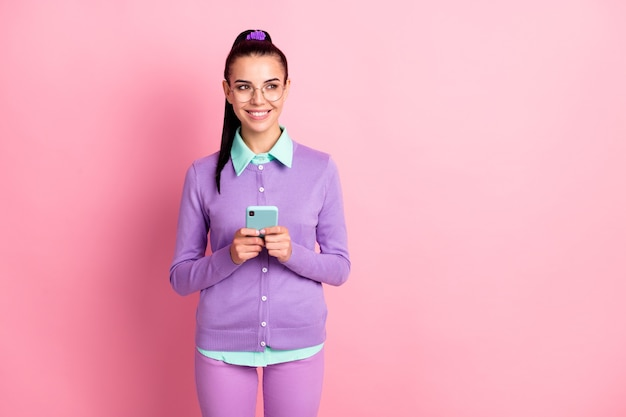 Photo of pretty lady hold telephone look empty space shiny white smile wear specs violet cardigan isolated pink color background