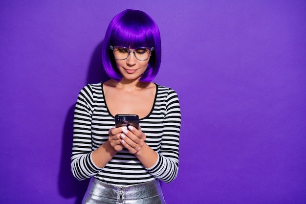 Photo of pretty lady holding hands new telephone writing email friends wear specs striped pullover isolated purple background
