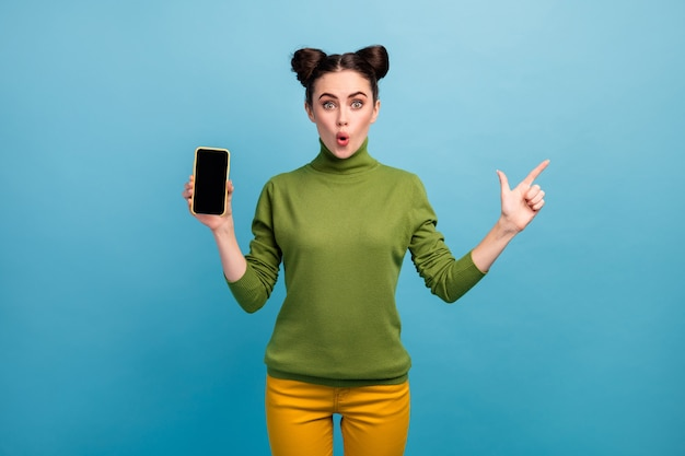 Photo of pretty lady sales manager hold new model smart phone direct finger side empty space open mouth wear green turtleneck yellow pants isolated blue color wall