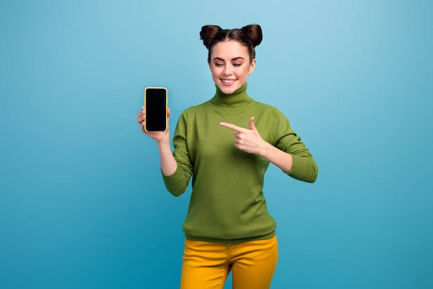 Photo of pretty lady sales manager hold new model smart phone show present advert amazing quality device wear green turtleneck yellow pants isolated blue color wall