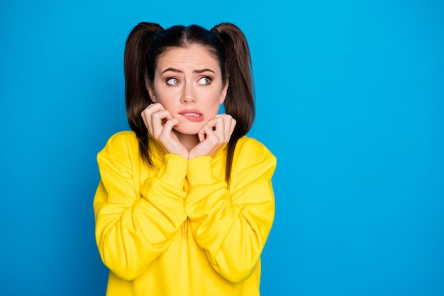 Photo of pretty lady two tails hairdo arms on cheekbones look fear side empty space made mistake uncomfortable situation wear yellow sweatshirt pullover isolated bright blue color background