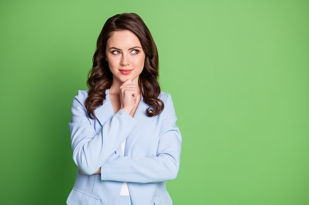 Photo of pretty lady wavy hairstyle hand chin look empty space wear blue blazer isolated green color background