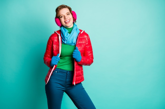 Photo of pretty lovely cute lady enjoy sunny winter day skating spend free time rejoicing wear casual red overcoat blue scarf pink ear covers trousers isolated teal color wall