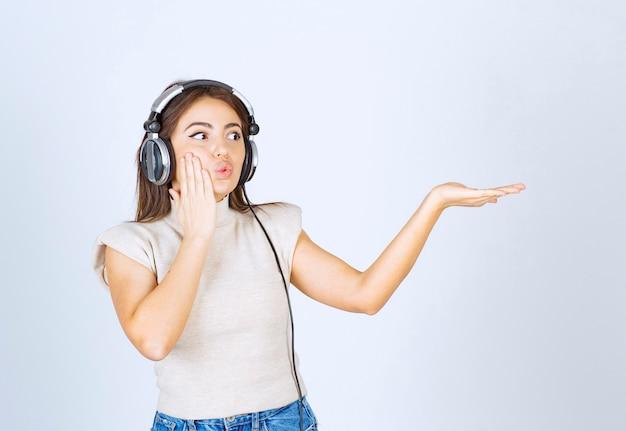 Foto di una bella donna modella ascoltando musica in cuffia e mostrando la mano.