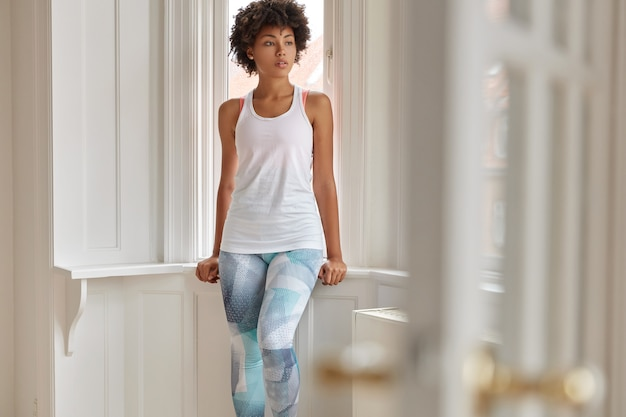 Photo of pretty relaxed fitness trianer rest at home after training, wears casual white vest and colorful leggings