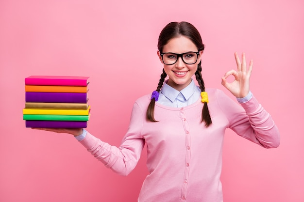 Photo of pretty student lady hold literature pile diligent pupil prefer reading not watching tv approve interesting story read books wear shirt pullover specs isolated pink color background