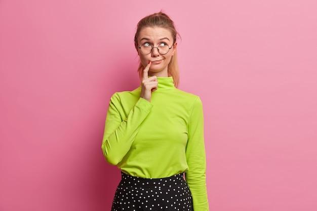 La foto della donna abbastanza premurosa tiene il dito vicino alle labbra ha un'espressione del viso confusa