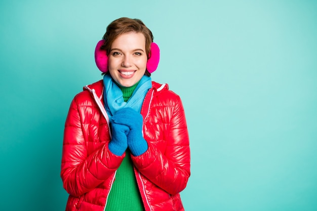 Photo of pretty traveler lady enjoy winter day buy new skaters want start skating wear stylish casual red overcoat blue scarf pink ear muffs isolated teal color wall