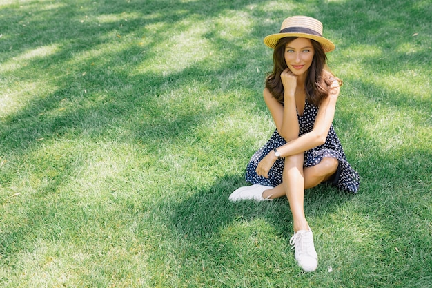 Photo of pretty woman dressed in summer hat and dress is sitting on the grass in summer park.
