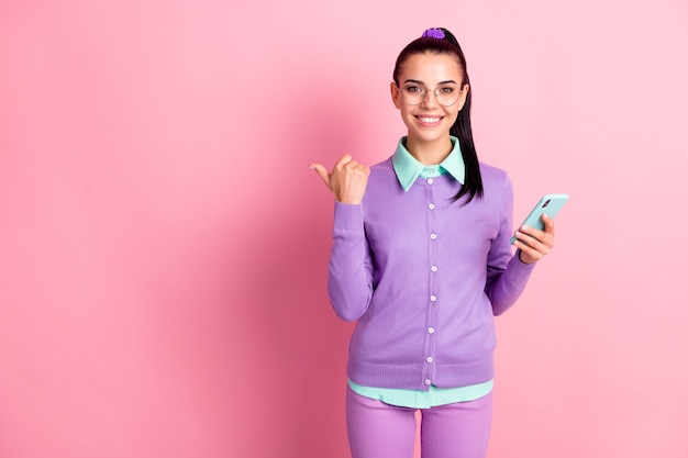 Photo of pretty woman hold telephone indicate finger empty space wear eyeglasses purple cardigan isolated pink color background