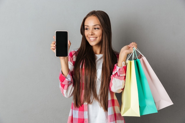 Photo of pretty woman holding shopping bags, showing blank mobile screen