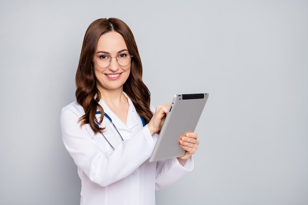 Photo of professional beautiful family doc lady hold modern technology tablet ebook online consultation quarantine wear specs stethoscope white lab coat isolated grey color background