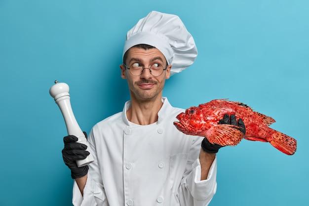 La foto del cuoco unico maschio professionista tiene il branzino rosso crudo e il macinapepe per condire, indossa l'uniforme del cuoco