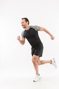 Photo in profile of content energetic sportsman 30s wearing shorts and t-shirt smiling and running marathon or doing workout