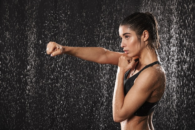 Photo in profile of focused athletic woman wearing black sportive bra punchning with clenched fist, isolated over rain drops background