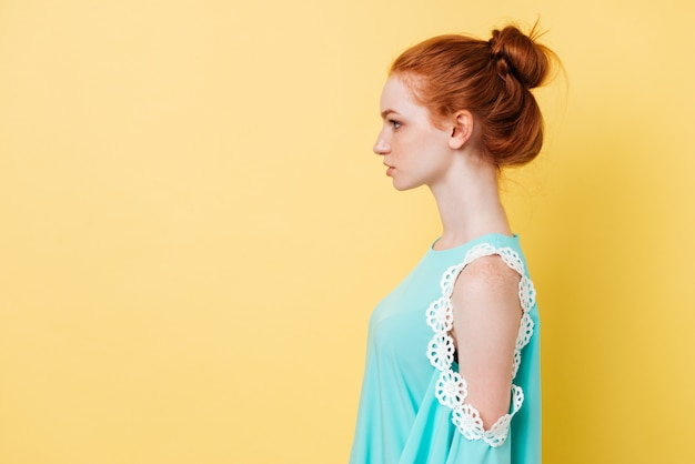 Photo in profile of pretty ginger woman in dress