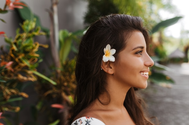 Photo in profile of young positive woman with tanned skin and flower in dark hair posing against wall of tropical plants