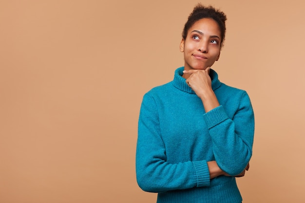 Photo of puzzled african american girl with curly dark hair wearing a blue sweater. touches chin can't decide, doubts, look up isolated over beige background with copy space.