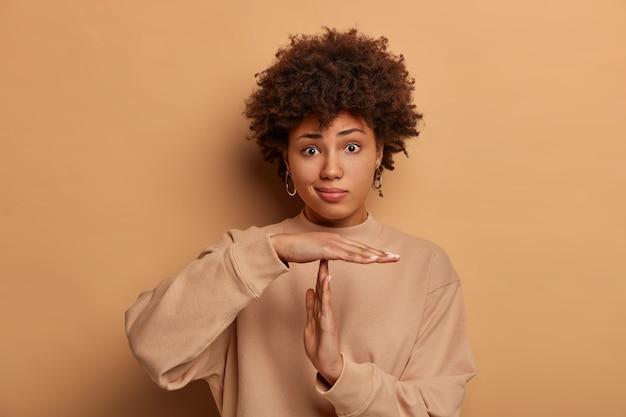 La foto di un woma dalla pelle scura perplessa fa un gesto di pausa, ha un'espressione seriamente frustrata, acconciatura riccia, vestito con una felpa casual, posa contro il muro beige, deve fermarsi