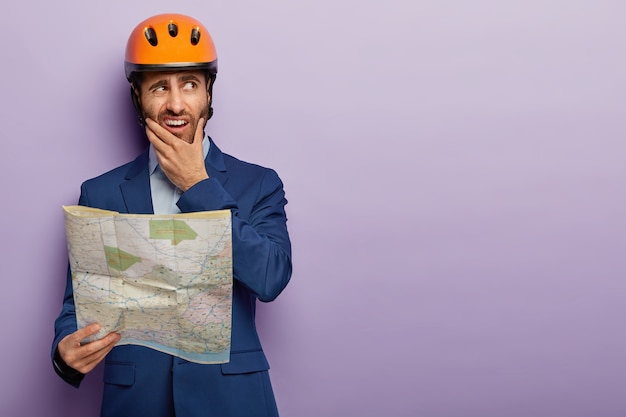 Photo of puzzled dissatisfied male engineer worker holds chin, holds blueprint, holds construction site map, works on building site, wears hard hat and blue suit