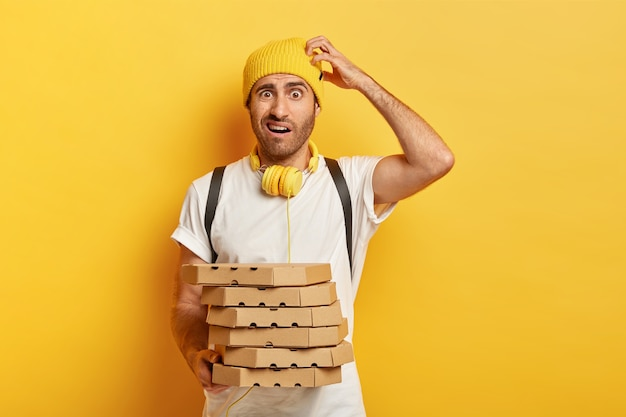 Photo of puzzled doubtful delivery man scratches head, holds takeaway pizza boxes, delivers fast food to customer, wears casual outfit, isolated on yellow wall. express delivering concept