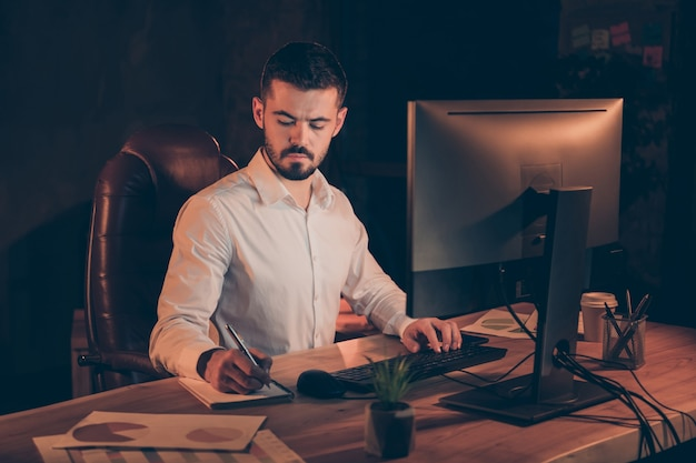 Photo of puzzled focused man noting typing pc