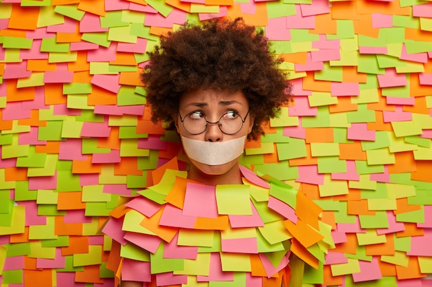 Photo of puzzled stressed afro woman with mouth covered by tape, has no freedom of speech, being kidnapped, looks embarrassed aside, wears spectacles, poses over paper wall with adhesive notes